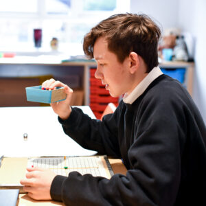 Student in Maths classroom using pins to create a tactile diagram