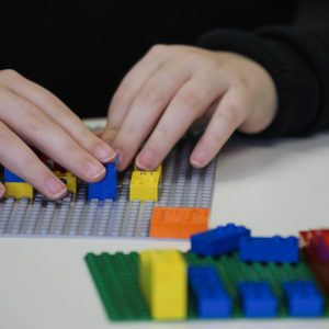 Close up of students reading braille on LEGO