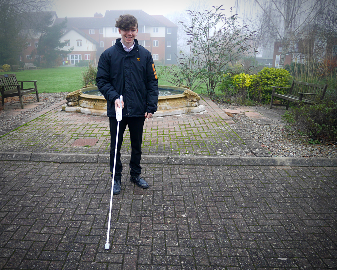Student stood with interactive cane outside school