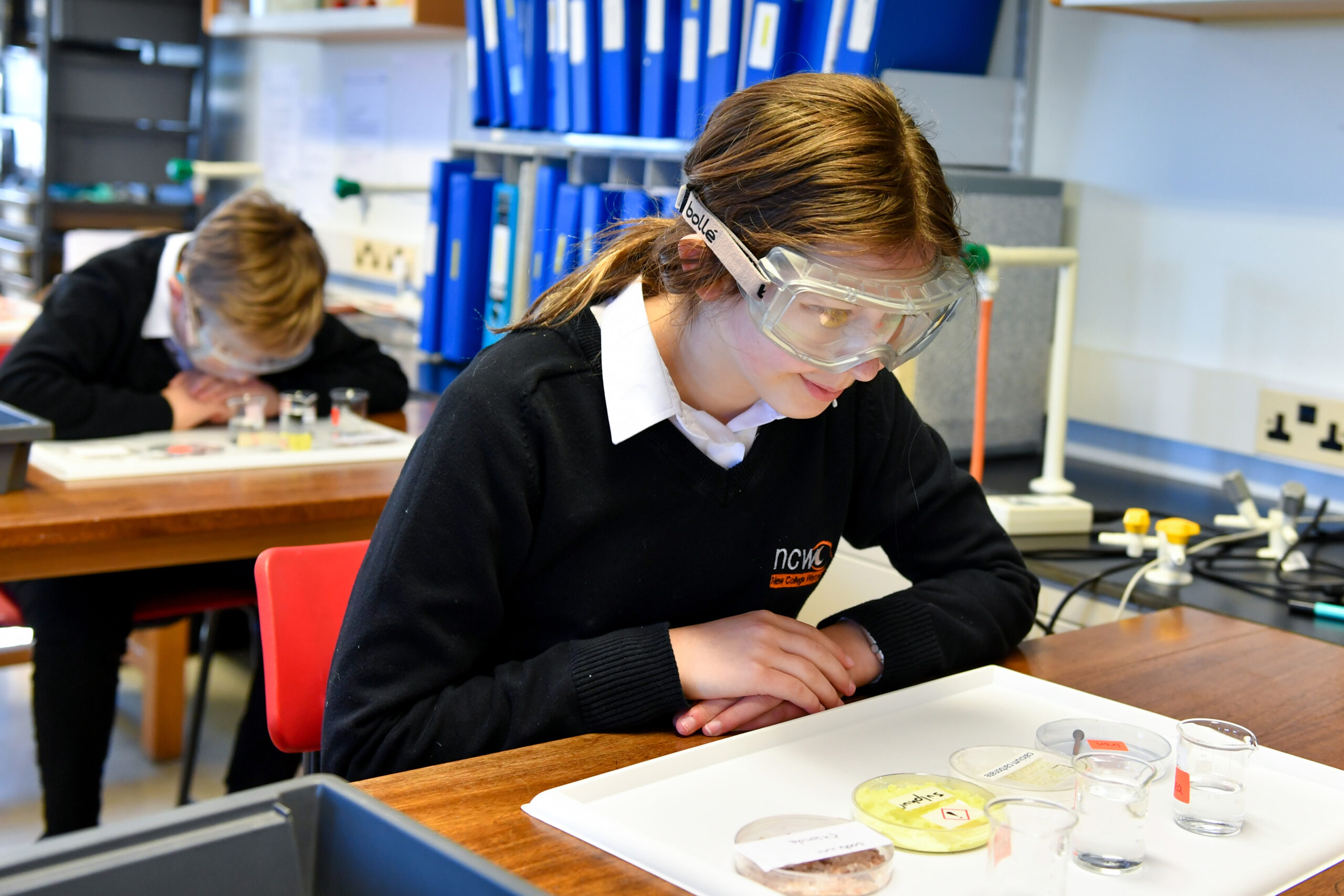 Student in Science lesson wearing protective eyewear and looking at different materials