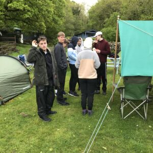 The team gathered around their tent pitch, looking glad to have some shelter!