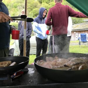 Bacon and sausages sizzling in the pan - students chatting in the background