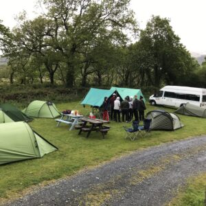 Wider view of the camp set up around two picnic benches and the NCW van in the background