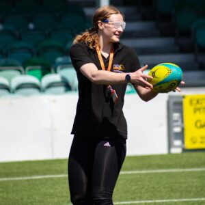 Megan from NCW Activities Team on the pitch catching the rugby ball - sim specs on