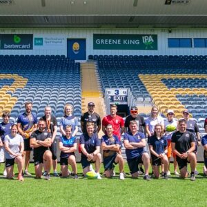 The whole group posing for a photo on the pitch
