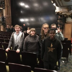 Another view of students in the theatre, all smiles looking at the camera