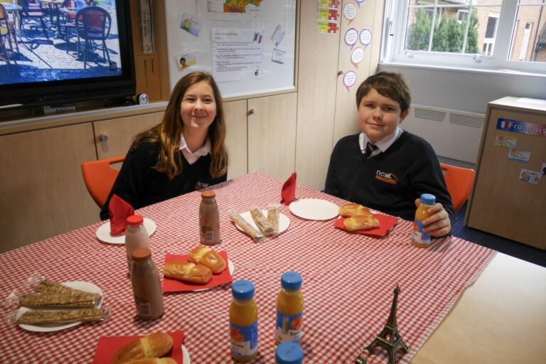 Students Amelie and Roman smiling at the camera, sat at the table with brioche and juice for their chosen breakfast