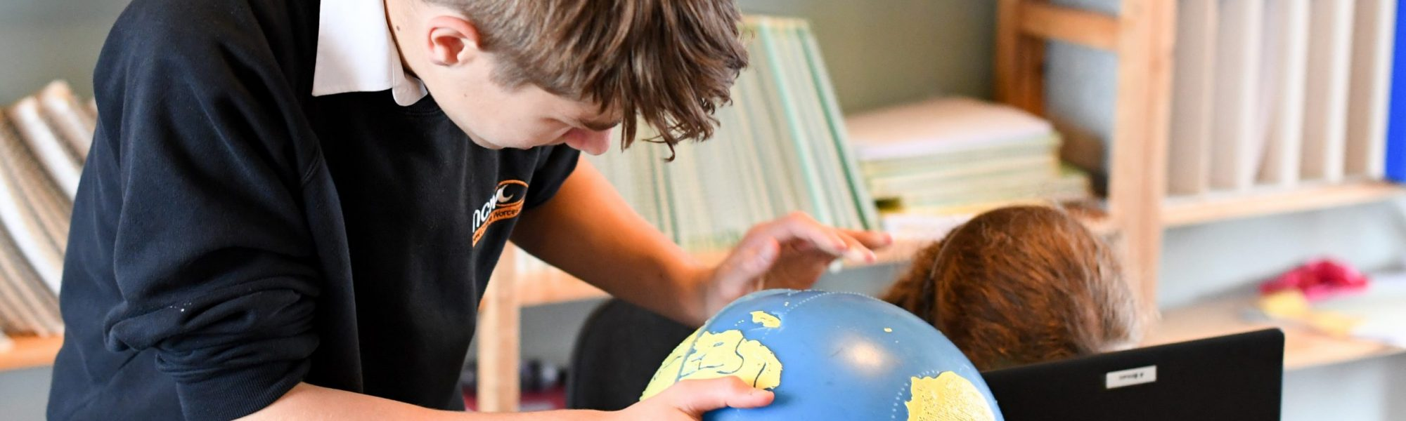 Student using a globe in Geography